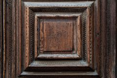 Fragment of an ancient Venetian door made of bog oak. Textured background, the texture of the wood.  royalty free stock image