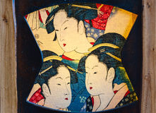 Fragment of the antique lamp. Japanese colorful female faces on the canvas Royalty Free Stock Photo