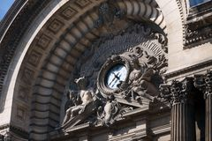 Fragment of architectural landmarks with a clock and ancient Greek gods on the old building of the National Bank of Romania royalty free stock images