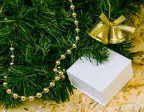 A fragment of artificial tree, a gift in a box, Christmas decora Royalty Free Stock Photos