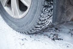 Fragment of automotive wheel with studded tires Stock Photos