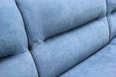 Fragment av baksidan av den blåa mjuka soffan royaltyfri foto