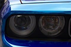 Fragment av den blåa sportbilen med billyktan Royaltyfria Bilder