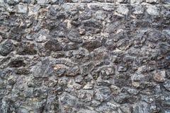 Fragment av den forntida medeltida gråa stenväggen som göras av olikt f arkivfoton