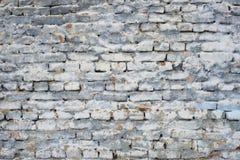 Fragment av den gamla tegelstenväggen med vitgrå färger och blåttfärger Royaltyfria Bilder