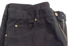 Fragment av den nya svarta jeansen på vit bakgrund Arkivfoto