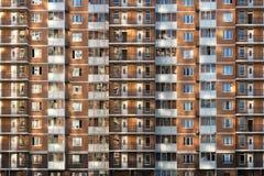 Fragment av en av de seriella höghushyreshusarna i Moskvaförorter med solnedgångilskna blicken på väggen och Arkivfoton