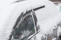 Fragment av en bil under ett lager av snö under tungt snöfall för processen av snölokalvård royaltyfri fotografi