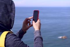 Fragment av en man med en ryggsäck i ett omslag med en huv på hans huvud som rymmer en telefon i ett rött fall mot det blåa vattn arkivfoto