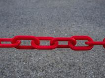 Fragment av en metallkedja av röd färg på bakgrunden av grå färgasfalt Fotografering för Bildbyråer