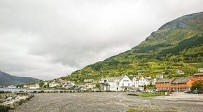 Fragment av ett fiskeläge på banken av en härlig fjord i en dimmig morgon, Norge royaltyfria foton