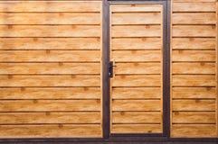 Fragment av ett träbrunt modernt staket med en ingångsdörr, closeup Bekläda beskådar Trästaket Ideas för modern stildesign arkivbild