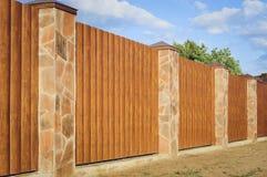 Fragment av ett träbrunt modernt staket med kolonner färdiga med stenen, närbild Trästaket Ideas för modern stildesign royaltyfria bilder