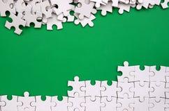 Fragment av ett vikt vitt pussel och en hög av uncombed pusselbeståndsdelar mot bakgrunden av en grön yttersida textur fotografering för bildbyråer