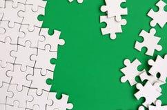Fragment av ett vikt vitt pussel och en hög av uncombed pusselbeståndsdelar mot bakgrunden av en grön yttersida textur arkivfoto