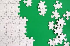 Fragment av ett vikt vitt pussel och en hög av uncombed pusselbeståndsdelar mot bakgrunden av en grön yttersida textur royaltyfria bilder