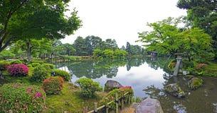 Fragment av japanträdgården med stenlyktan och den stora mossiga rocen Arkivbilder