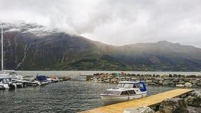 Fragment av pir i Surfjorden nära staden av Odda, Norge Sikt av den stora bergplatån med dess massiva glaciärer royaltyfri bild