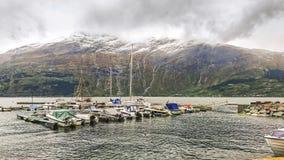 Fragment av pir i Surfjorden nära staden av Odda, Norge Sikt av den stora bergplatån med dess massiva glaciärer royaltyfria foton