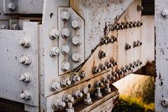Fragment av rostiga metallstrukturer av den gamla järnvägsbron Korrosion och gamla målarfärgbultar och bromuttrar Arkivfoton