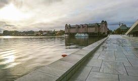 Fragment av staden av Oslo i strålarna av solnedgången över Östersjön, Norge arkivfoto