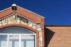 Fragment av taket av huset mot himlen Arkivfoto