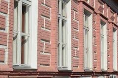 Fragment av tegelstenväggen av med fönster Arkivfoto