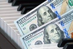 Fragment av två hundra dollarsedlar på pianotangenter royaltyfri fotografi