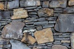 Fragment av väggen som göras av stenar av olik typer och form Arkivfoto