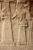 Fragment of babylonian limestone funereal stele. Babylonian limestone funereal stele with relief sculpture of the governor of Mari and Suhi praying to the Gods stock image