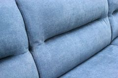 Fragment of the back of the blue soft sofa. royalty free stock photo