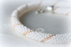Fragment of beaded necklaces in white and gold beads. On textile background Stock Image