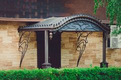 beautiful one-story house, a porch with an iron canopy. royalty free stock images