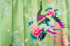 Fragment of beautiful silk fabric with the image of flowers and. Beautiful silk fabric of light green color with the bright image of a peacock among flowers.g Royalty Free Stock Photography