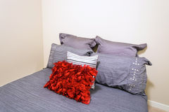 Fragment of bedroom. Fragment of modern grey bedroom interior with red and silver designer pillows in a luxury house Stock Photos