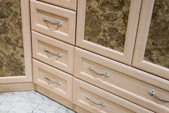 Fragment of beige cupboard with drawers Royalty Free Stock Photography