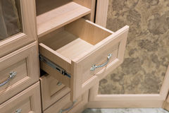 Fragment of beige cupboard with drawers Royalty Free Stock Photos