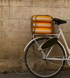 Fragment of a bicycle with decorative wheels on the trunk against the background of the wall on the street. royalty free stock image