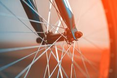 A fragment of a Bicycle wheel. Spoke Brilliant. The bike is blue. A small depth of field. The background is blurred royalty free stock images