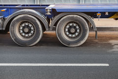 Fragment of big truck, wheels on dark asphalt road Stock Photo