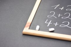 Fragment of Black Chalkboard with Hand Written Simple Mathematics Equations Broken White Chalks. Back to School Concept stock photos