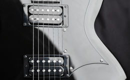 A fragment of a black guitar with steel strings. Dark background Stock Photo