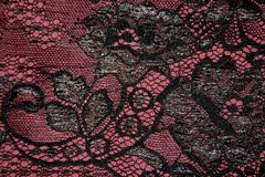 Fragment of black lace against the background burgundy color fab. Close-up fragment of black lace against the background burgundy color fabric Stock Photography