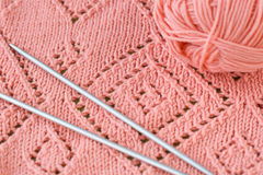 A fragment of a blankets, pink skein of yarn and knitting needles Stock Image
