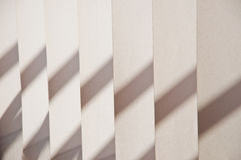 Fragment of blinds. A beige fabric with shadow close up Stock Photos