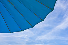 Fragment of a blue garden umbrella against the sky with clouds. Royalty Free Stock Photo