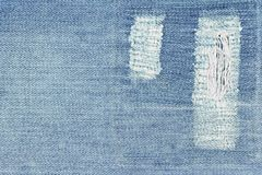 Fragment of blue jeans with patch. Royalty Free Stock Photography