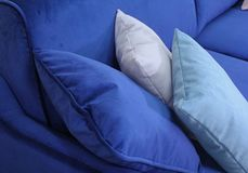 A fragment of a blue velvet sofa with three pillows. royalty free stock photo