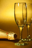Fragment of a bottle of champagne and glasses Royalty Free Stock Image