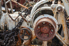 Fragment of bow anchor winch on abandoned ship Stock Photos